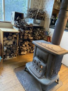 cast iron stove with fire inside next to stacks of cut wood